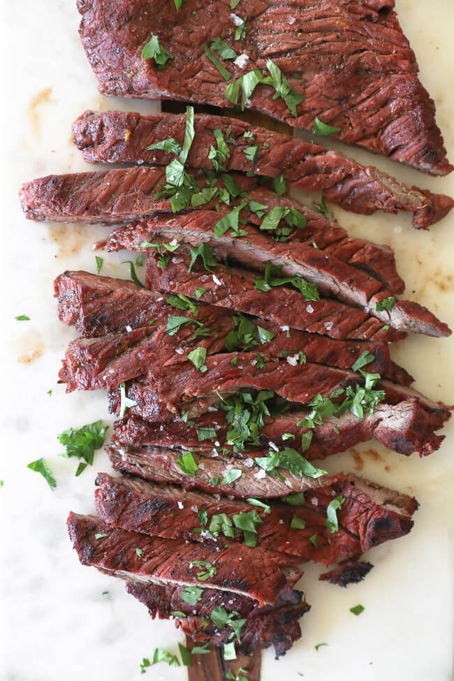 Carne asada steak on a board cut into strips topped with salt and cilantro overhead vertical image