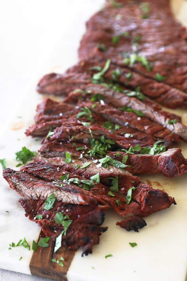 Quick and easy carne asada on a board cut into strips topped with cilantro close up angle shot