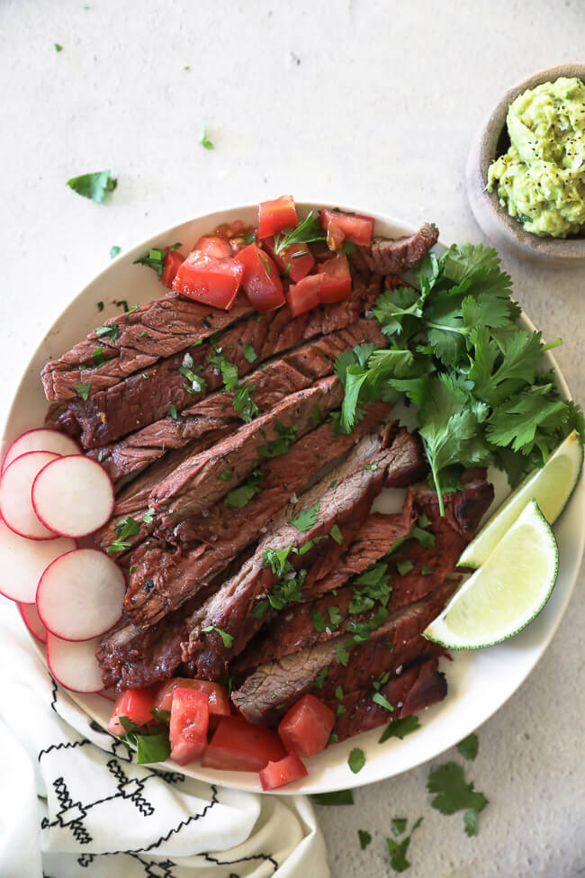 Carne asada steak strips on a plate with radish, tomato, cilantro and lime