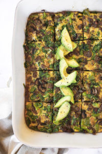 Keto breakfast casserole sliced in a dish with sliced avocado topping overhead vertical image
