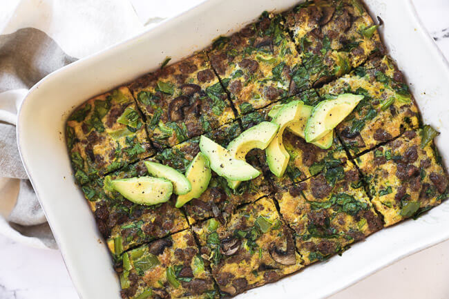 Keto breakfast casserole sliced in a dish with avocados on top