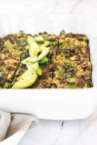 Keto breakfast casserole sliced in a dish with sliced avocado close up angle image