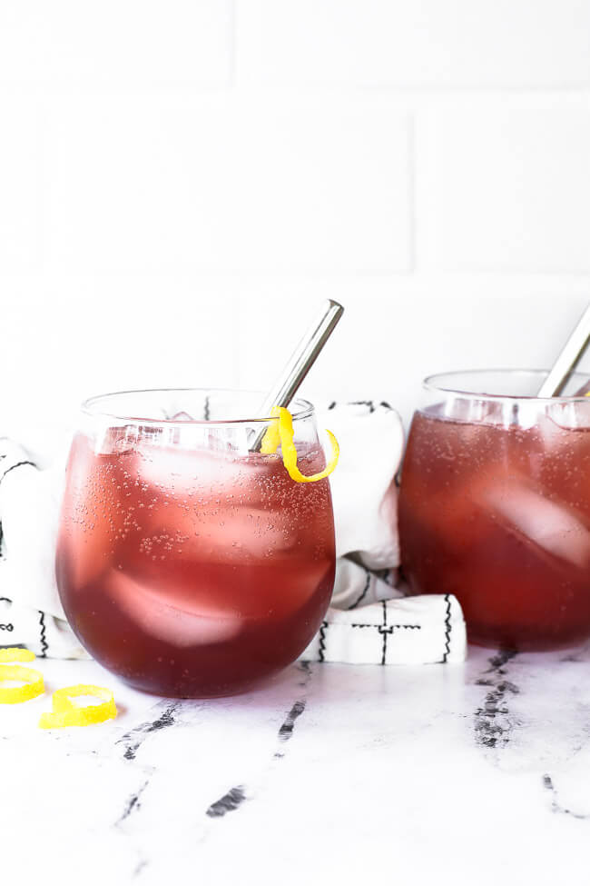 Two glasses of pink vodka lemonade with stainless steel straws and lemon rind garnish.