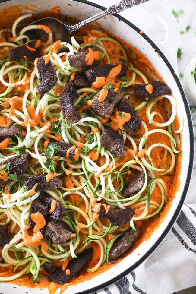 Close up vertical image of zoodles and orange sauce with steak bits in a pan