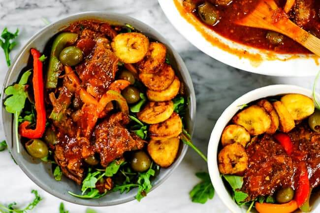 Ropa vieja served in bowls with greens and fried plantains.