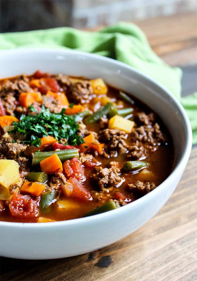 Hamburger soup in a bowl with green beans, carrots, tomato and parsley