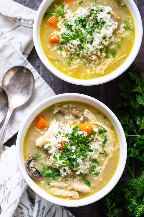 Two bowls of chicken soup with cauliflower rice, carrots and parsley