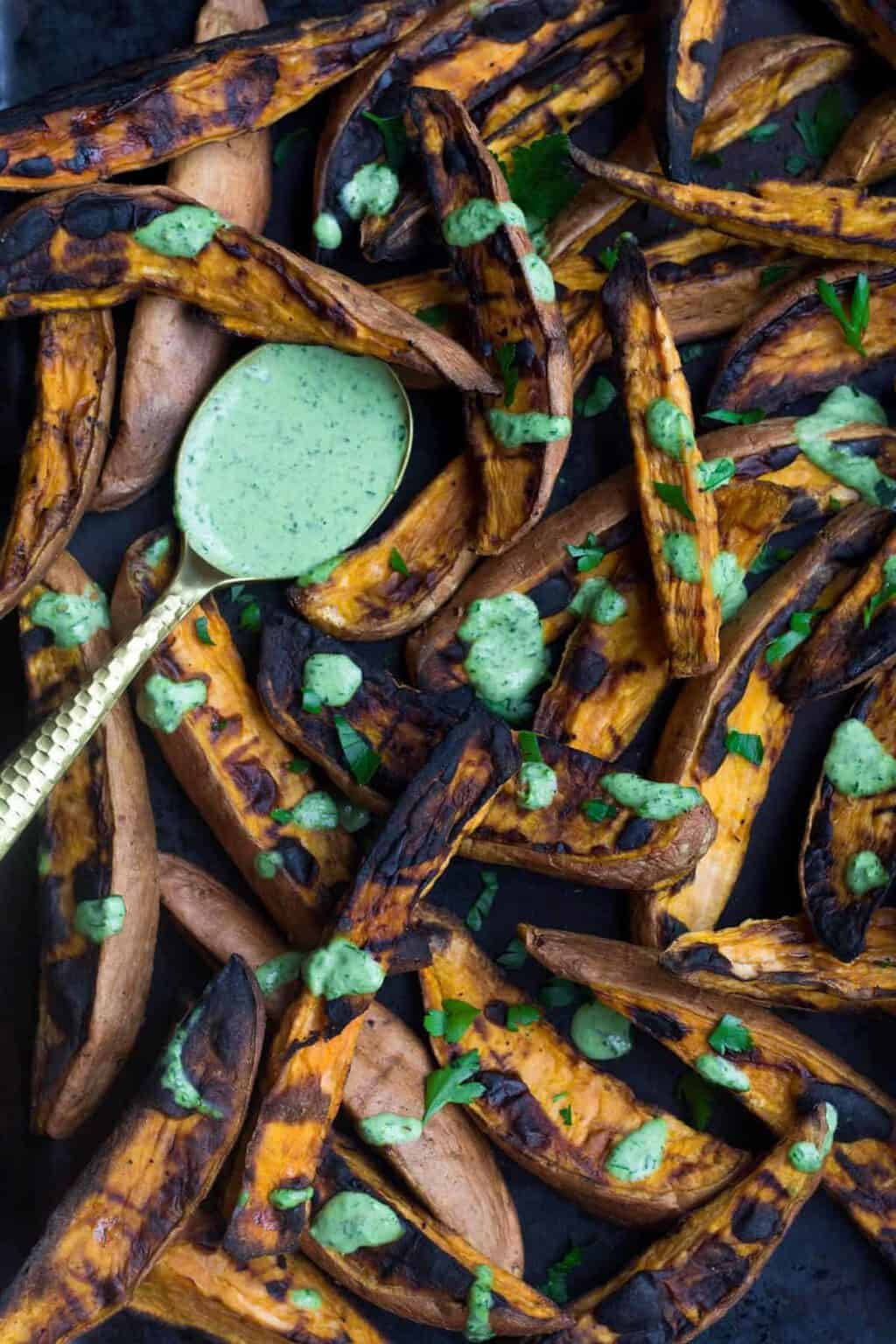 Close up of grilled sweet potato fries on a pan with green sauce all over