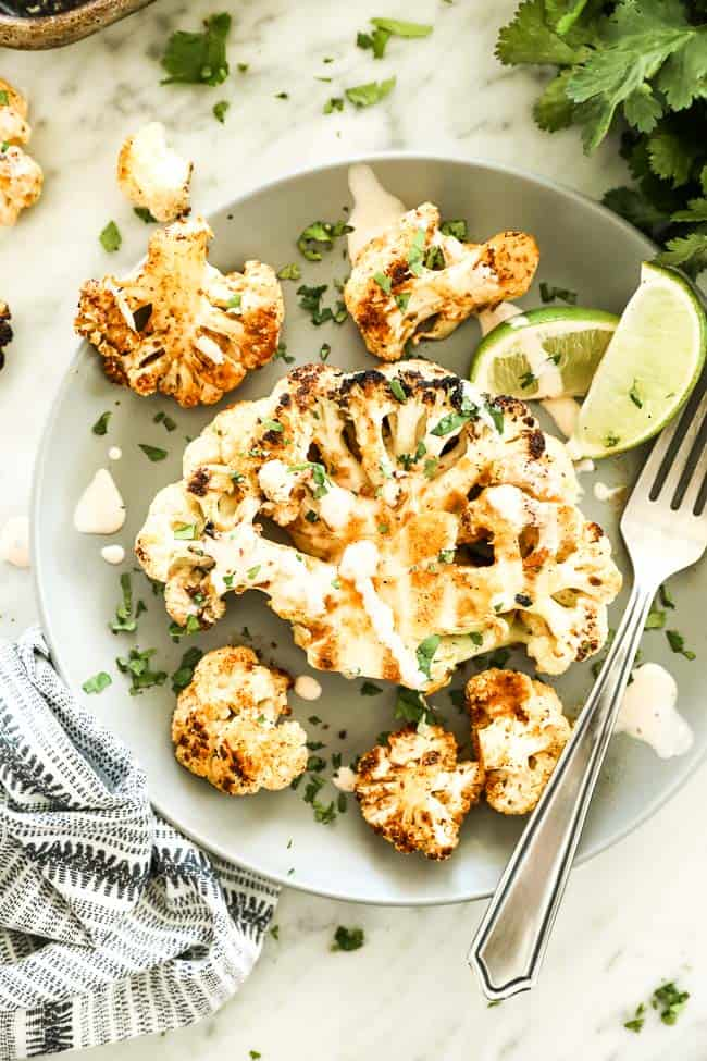Grilled cauliflower steak on a plate with sauce on top