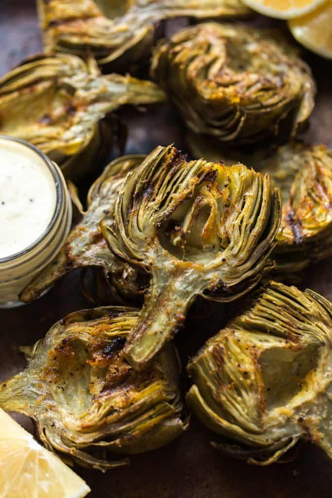 Grilled artichokes stacked on a sheet pan