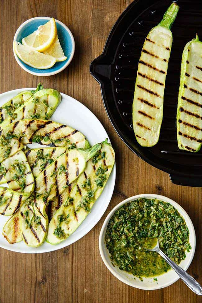 Grilled zucchini slices on a plate with pieces in a cast iron skillet on side