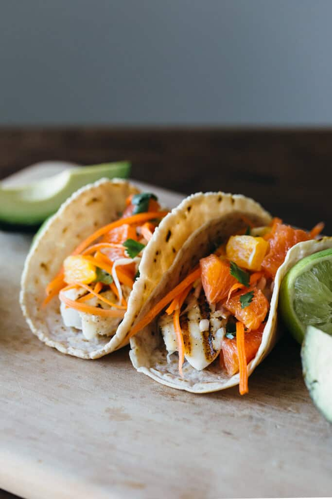 two grilled fish tacos on a cutting board with slaw topping
