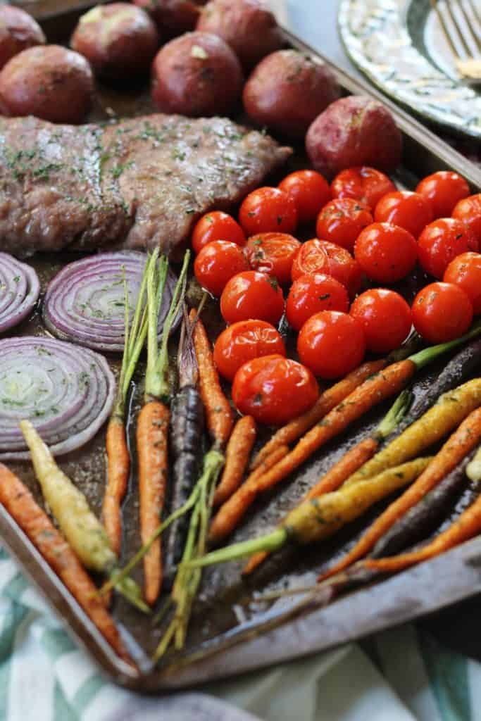 Butter herb steak and veggies on sheet pan with carrots, potatoes and onion