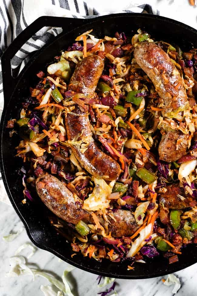Sausage and cabbage skillet in a large cast iron skillet.