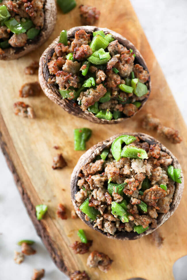 sausage stuffed mushrooms with chopped green peppers on board overhead close up vertical image