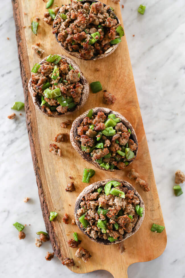 sausage stuffed mushrooms with chopped green peppers on board overhead vertical image