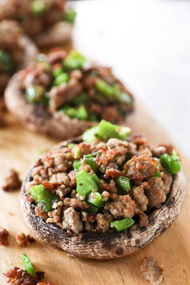 sausage stuffed mushrooms with chopped green peppers on board angle close up image
