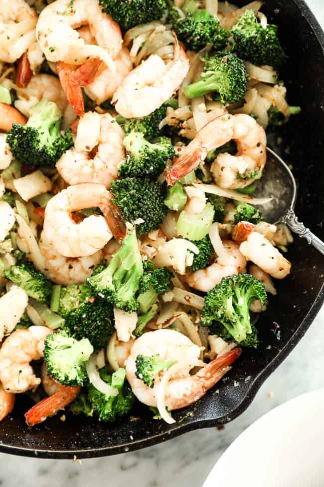 Image of seafood stir-fry cast iron skillet with serving spoon in pan. Stir fry has shrimp, white fish, broccoli, celery and onion and cajun seasoning.