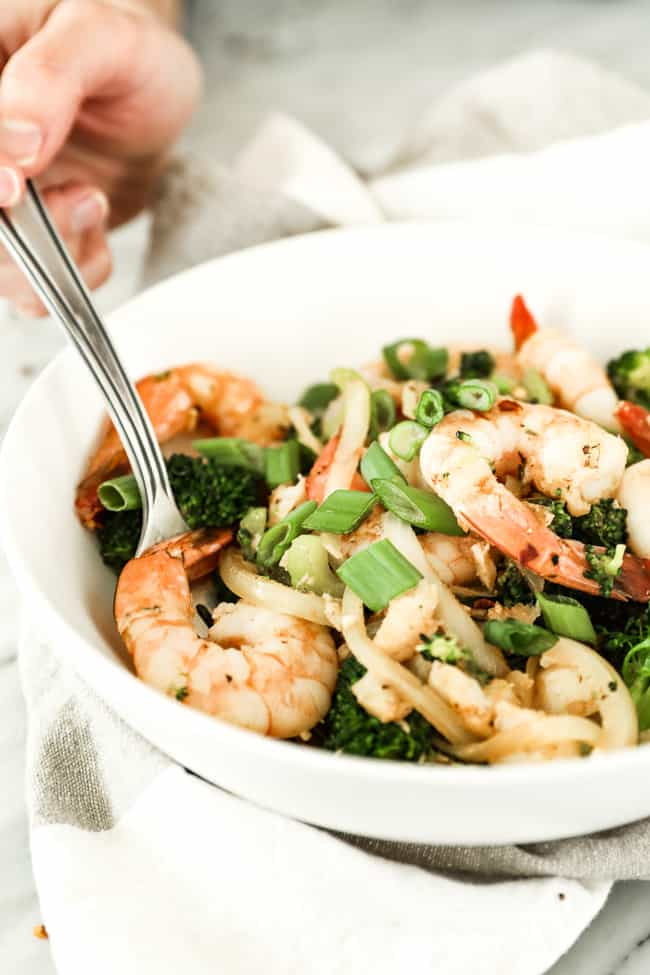 Image of seafood stir-fry served in a bowl with shrimp, white fish, broccoli, celery and onion and cajun seasoning. Holding fork in bowl topped with chopped green onion and red pepper flakes.