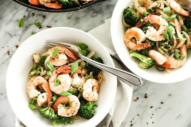 Image of seafood stir-fry served in two bowls, with shrimp, white fish, broccoli, celery and onion and cajun seasoning. Topped with chopped green onion and red pepper flakes.