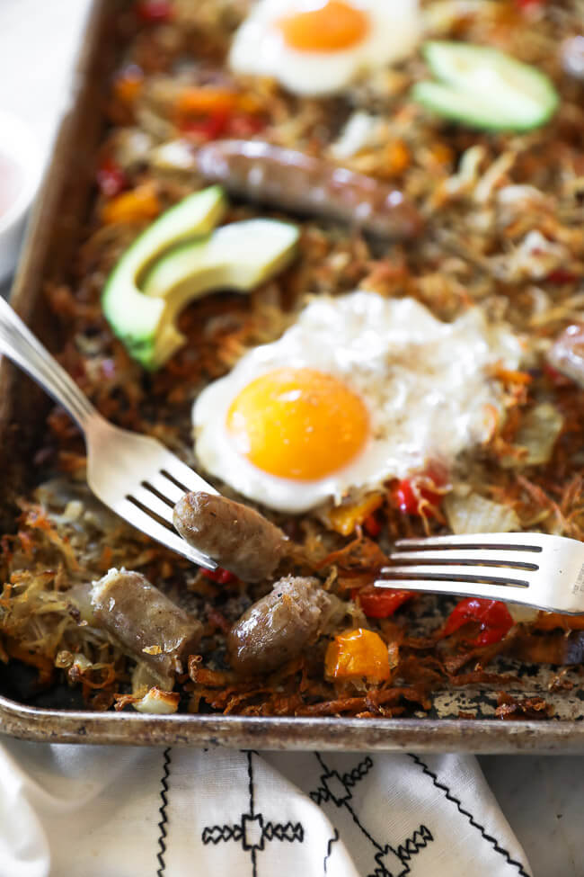 Close up angled shot of sheet pan breakfast bake with sausage cut up and a bite on one fork on the pan.