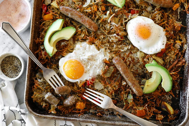 Sheet pan breakfast bake on a large sheet pan with hash browns, eggs, bell pepper and onion. Topped with avocado slices and two forks dug in on the pan.