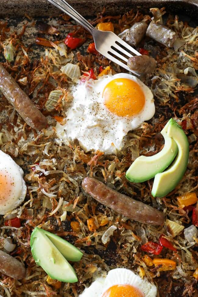 Close up image of sheet pan breakfast bake. Bake consists of hash browns, bell pepper, onion, sausages, eggs and topped with avocado.