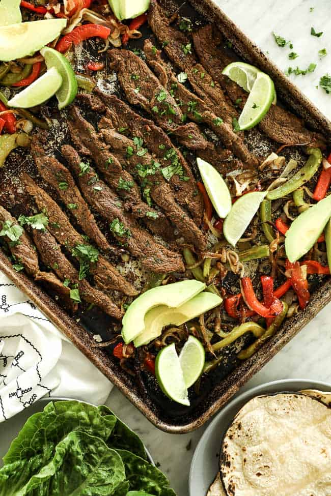 Overhead vertical image of sheet pan fajitas on sheet pan with steak, green and red bell peppers and onion. Topped with fresh cilantro, avocado slices and lime wedges.