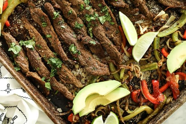 Horizontal overhead image of sheet pan fajitas on sheet pan. Made with steak, green and red bell peppers and onion. Topped with sliced avocados, lime wedges and fresh chopped cilantro.