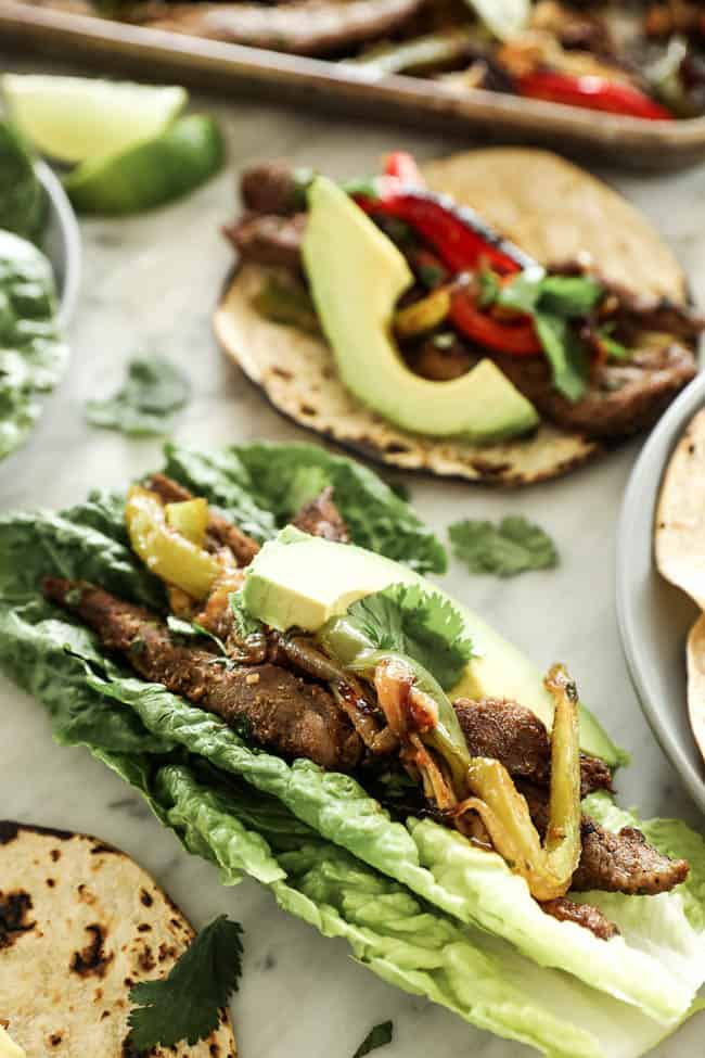 Angled image of sheet pan fajitas in romaine lettuce leaves with avocado and cilantro on top.