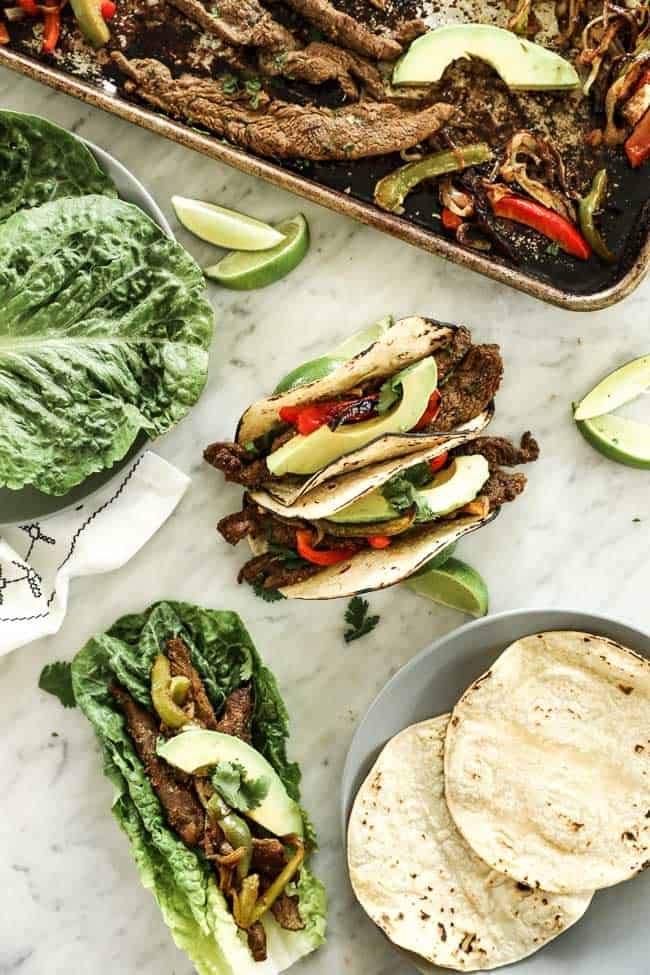 Vertical overhead image of sheet pan fajitas served in soft taco shells and also in romaine lettuce leaves. Topped with sliced avocado and fresh cilantro.