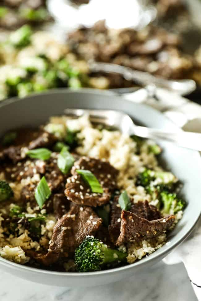 Angled shot of sesame beef in a bowl with cauliflower rice and broccoli. Topped with chopped green onion and sesame seeds.