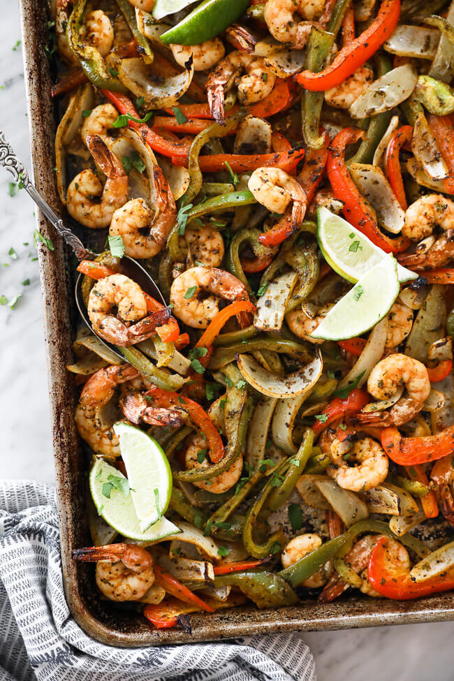 sheet pan shrimp fajitas on a pan with onions, bell pepper and lime wedges overhead vertical image
