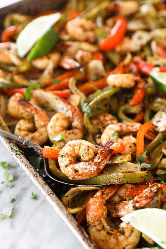 sheet pan shrimp fajitas on a pan with onions, bell pepper and lime. Spoon scooping up shrimp