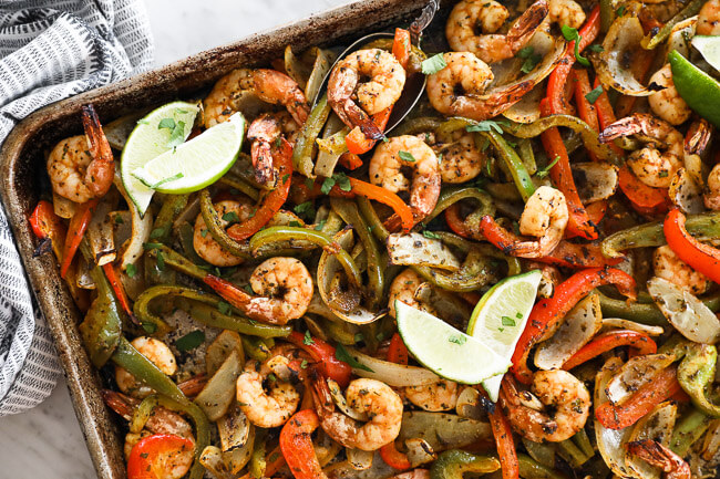 sheet pan shrimp fajitas on a pan with onions, bell pepper and lime wedges overhead horizontal image