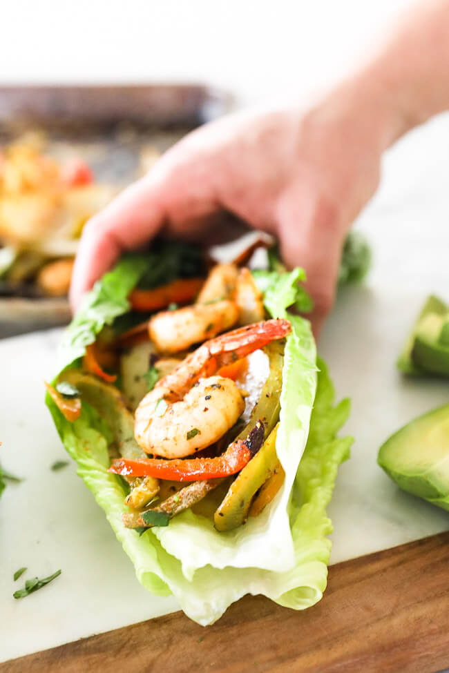 Shrimp, onions and bell pepper in lettuce shell with hand picking up close up angle