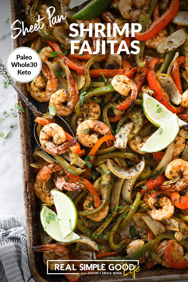 sheet pan shrimp fajitas on a pan with onions, bell pepper and lime wedges overhead vertical image with text at top
