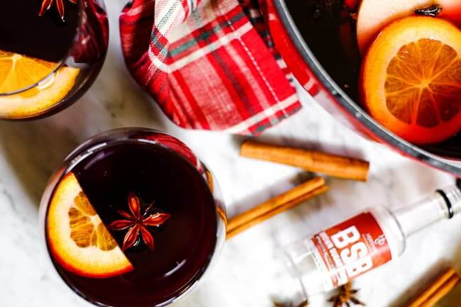Simple mulled wine recipe in glasses with orange slices, cinnamon sticks, a plaid napkin, star anise and bourbon bottle.