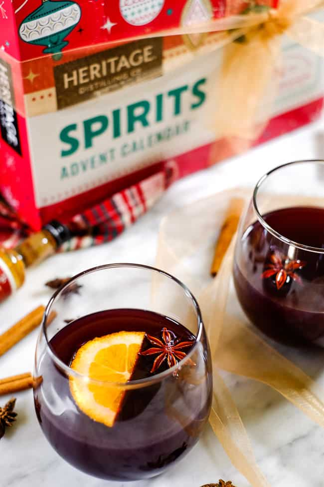 Simple mulled wine recipe in glasses garnished with orange slices and star anise. Cinnamon sticks and Heritage Distilling Company advent calendar in the background.