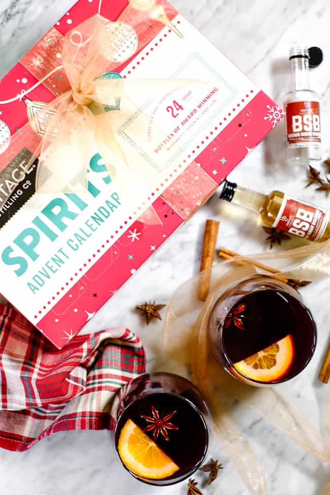 Simple mulled wine recipe in glasses with cinnamon sticks, orange slices, star anise, bourbon bottles and the Heritage Distilling Company 2018 advent calendar.