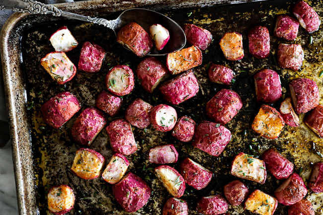 Roasted radishes on sheet pan with spoon horizontal image