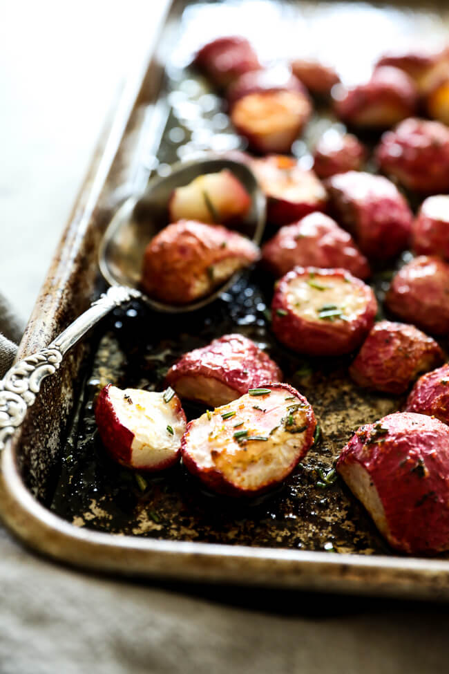 Roasted radishes on sheet pan with spoon close up at an angle vertical image