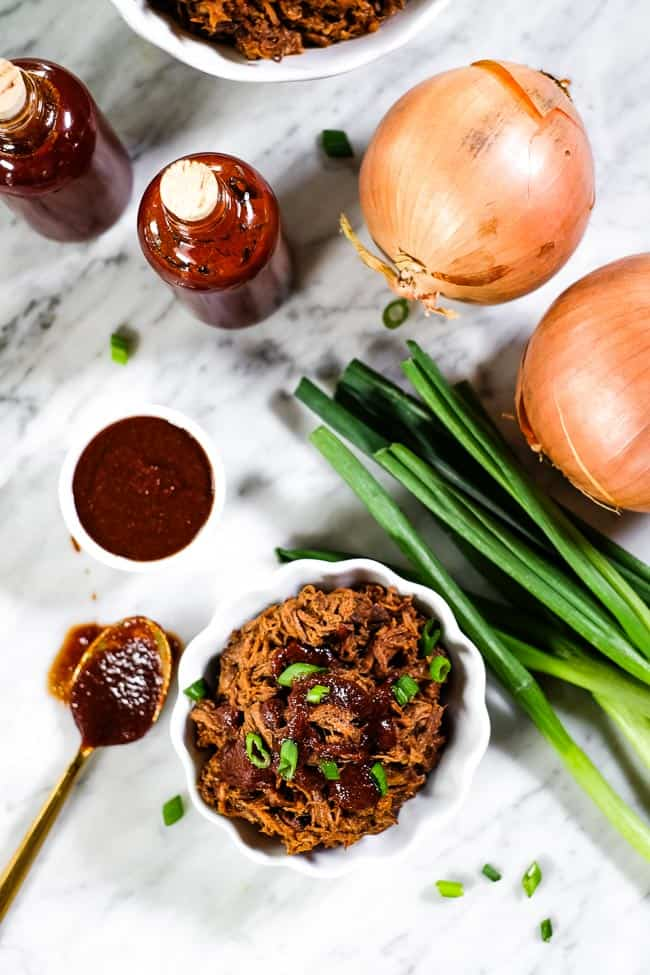 Slow cooker BBQ beef in a ramekin with BBQ sauce and chopped green onion on top. Extra sauce and onions on the table.