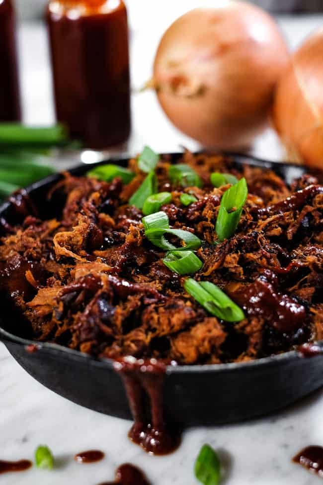 Angle shot of slow cooker BBQ beef in cast iron skillet with extra BBQ sauce and chopped green onion on top.
