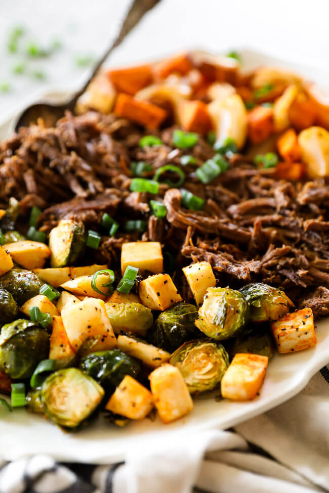 Close up angle shot of shredded slow cooker beef pot roast on platter with roasted veggies on each side