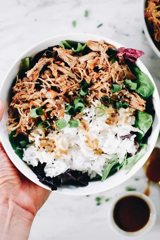 Slow cooker teriyaki chicken in a bowl with white rice, greens and teriyaki sauce