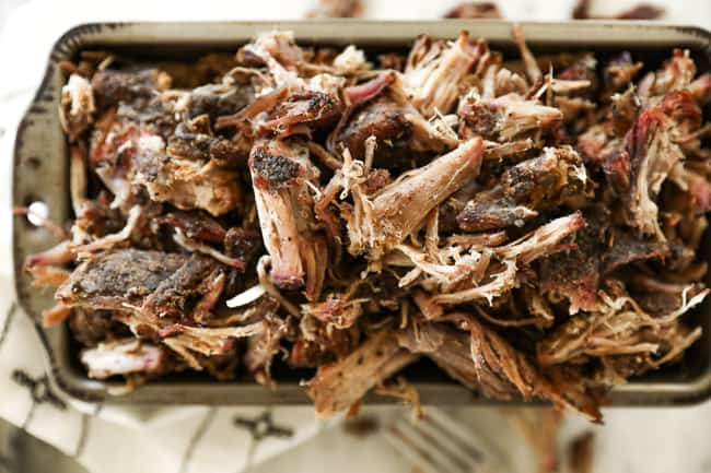 Horizontal image of smoked pork shoulder shredded in a pan