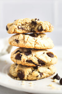 Stack of 4 vegan chocolate chip cookies and the top one has a bite taken out of it.