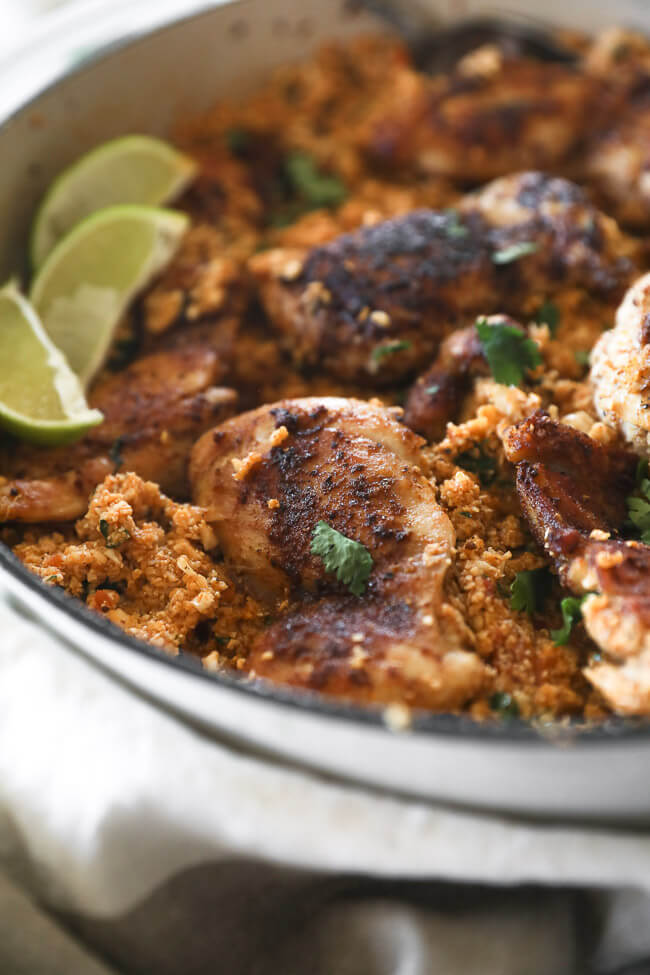 Spicy chicken thighs and cauliflower rice in pan with lime wedges angled close up vertical shot