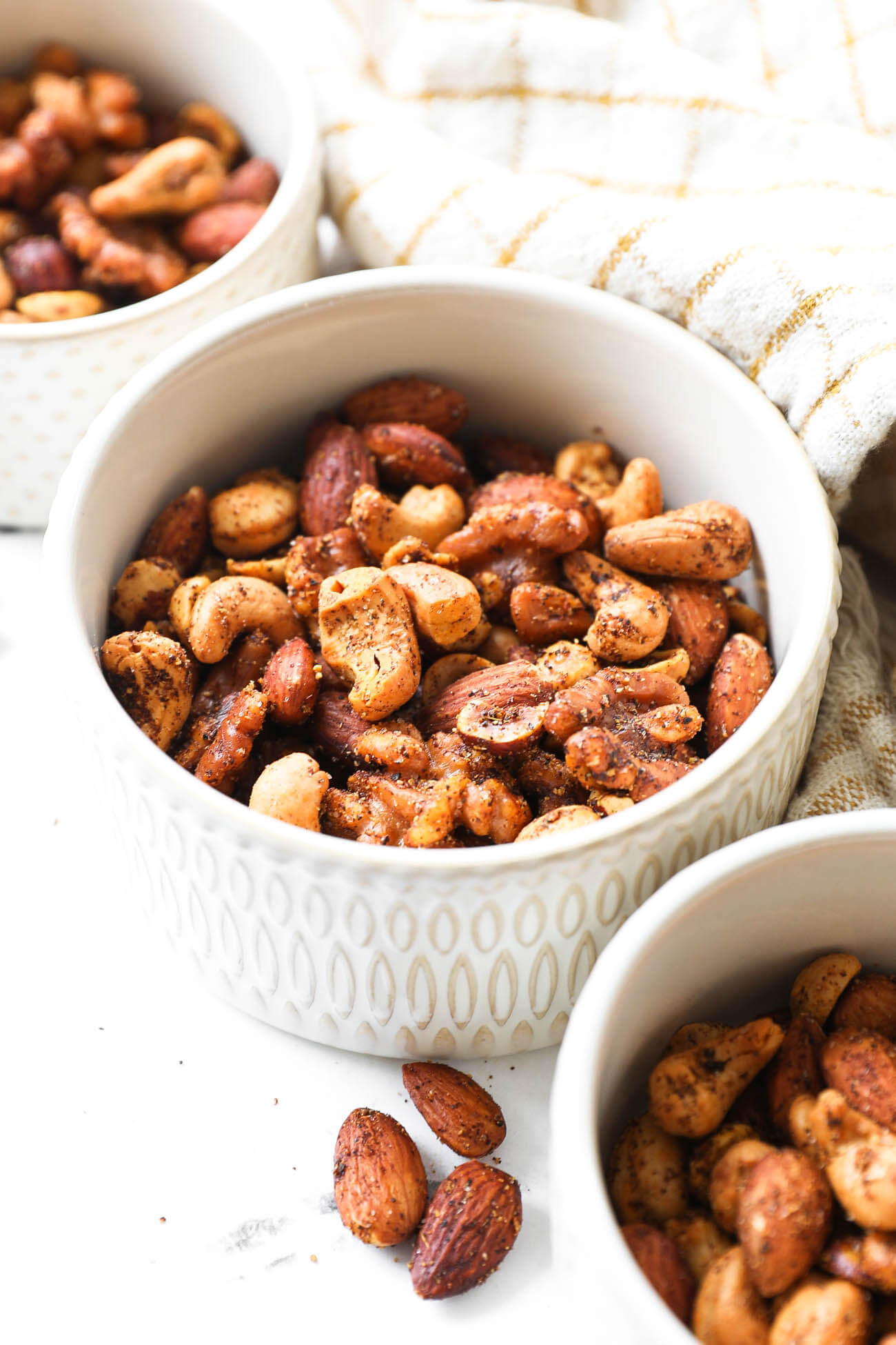 Close up angle shot of ramekin full of homemade spicy nuts including walnuts, almonds, cashews and hazelnuts